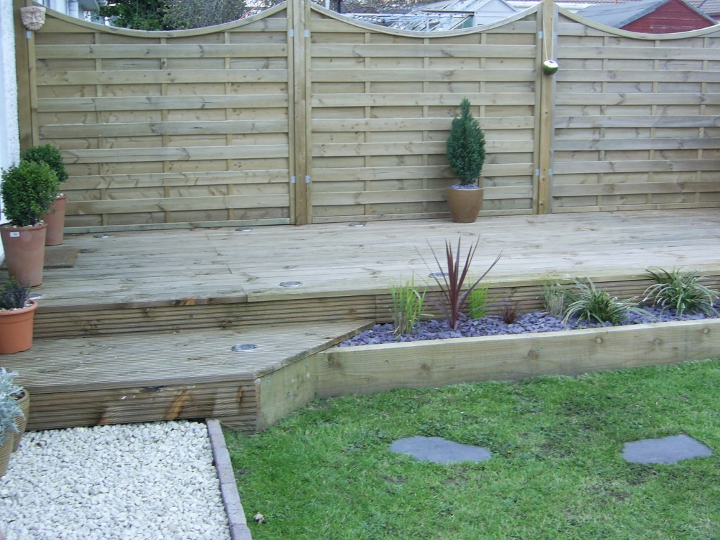 Decking and fencing installed, bespoke railway sleeper plant beds and all planted up to clients specification